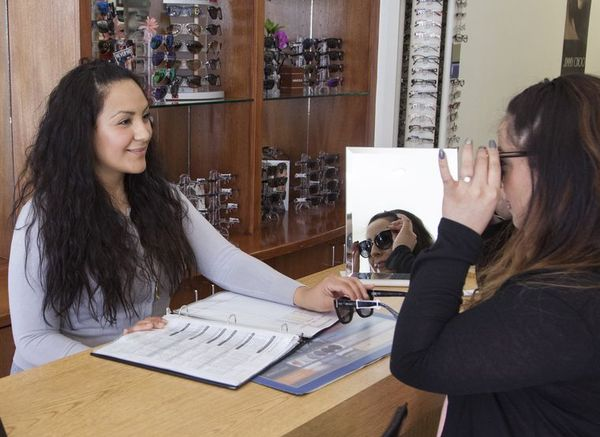 optician selecting eyeglass frames in Northridge